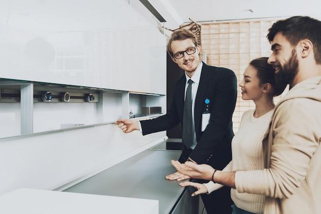 スーツを着たマネージャーがカップルに新しいキッチンを見せています。