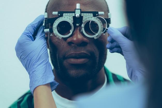 Взрослый мужчина пациент на оптическом обследовании в клинике