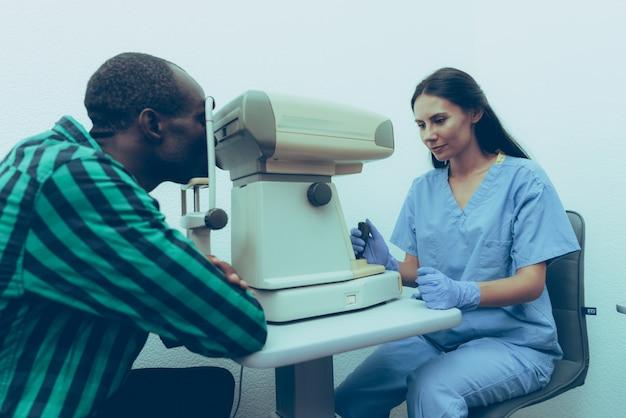 女医は患者の目を調べています