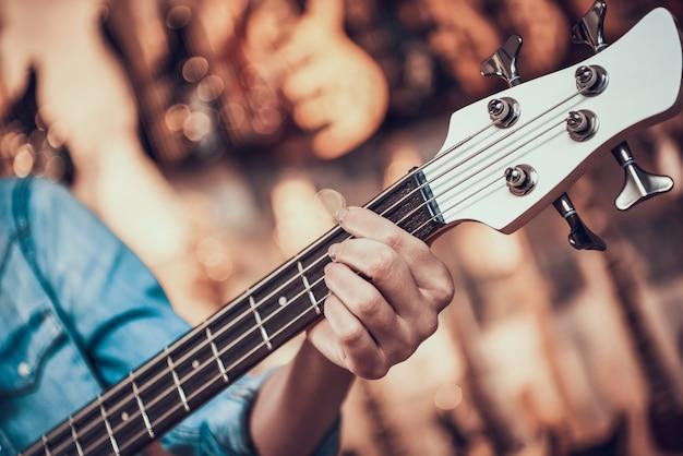 女性はミュージカルストアでエレキギターでフレットをクランプします。