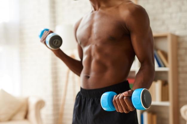 Афро-американский спортсмен, накачивая мышцы гантелями
