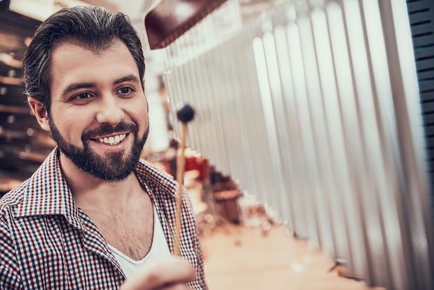 ひげを生やした男が音楽店でバーチャイムを演奏します。