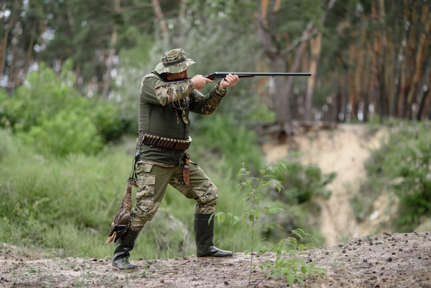 Охотник с оружием на охоте на птиц в летнем лесу.