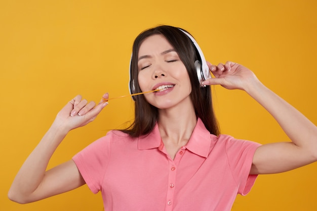 アジアの女の子は、ガム、ヘッドフォンの分離でポーズをとっています。