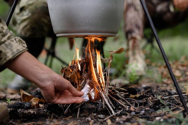 Рука человека поджигает под котелок в лесу.
