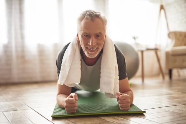 Счастливый мотивированный пожилой мужчина делает упражнение на доске