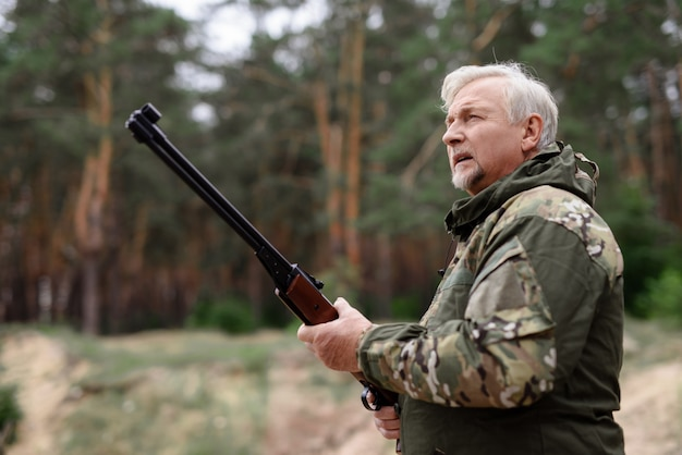 Внимательный охотник человек с ружьем, глядя вверх.
