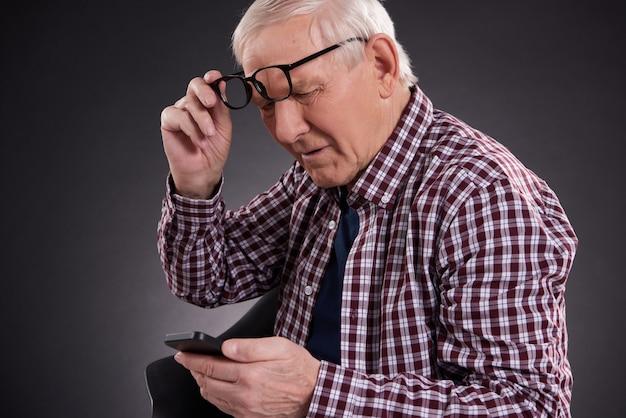 老人は彼の眼鏡を持ち上げて、電話に見えます