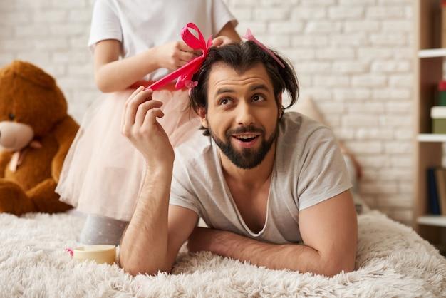 ギフト用のリボンとピグテールで思いやりのある子女の子ネクタイお父さん髪
