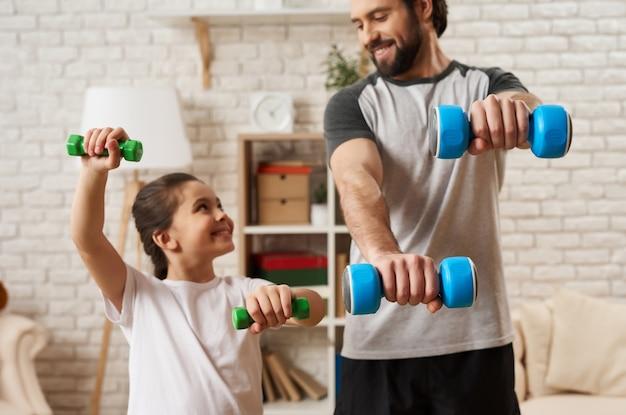 Папа и дочь делают упражнения с гантелями