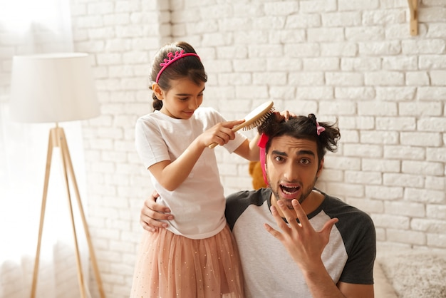 アラブ家族の女の子はお父さんのための新しいお父さんの髪型を作っています。