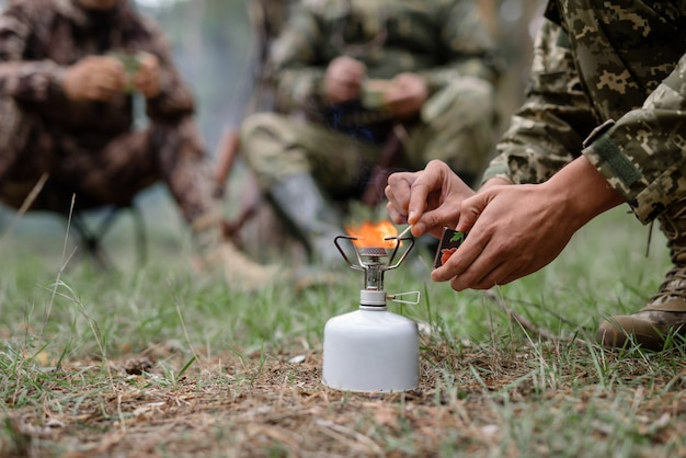 Охотник поджигает портативную газовую плиту на пикнике.
