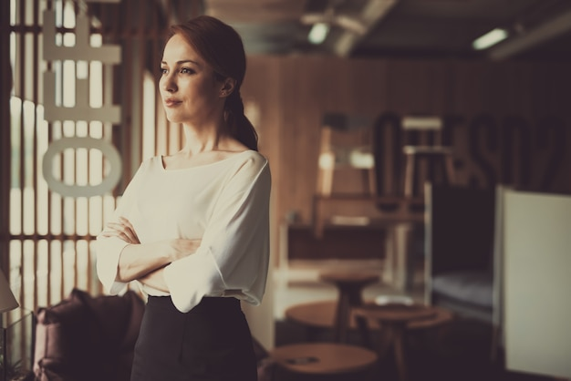 Молодая женщина стоит в офисе подбоченясь