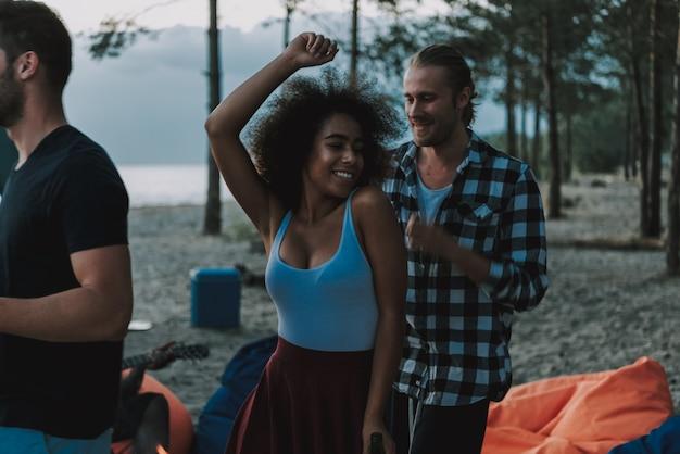 アフロアメリカンギタリストのビーチで人々のダンス