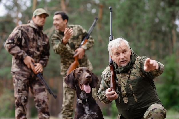 家族の男と息子のポインター犬と一緒に狩り。