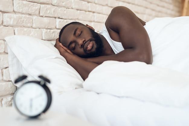 Афро-американский мужчина спит в постели рядом с будильником