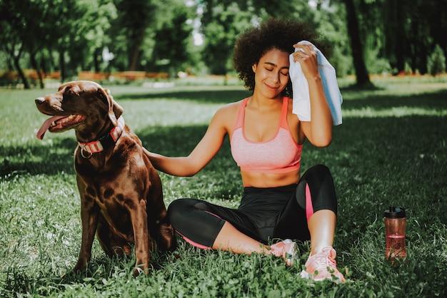 茶色の犬をかわいがる草の上に座っている美しい女性。