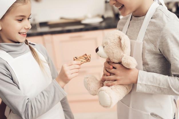 キッチンで遊ぶ子供たちがテディベアにクッキーを贈る。