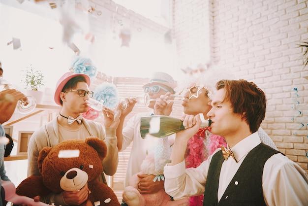ゲイの人々はシャンパンを飲み、同性愛者のパーティーでリラックスします。