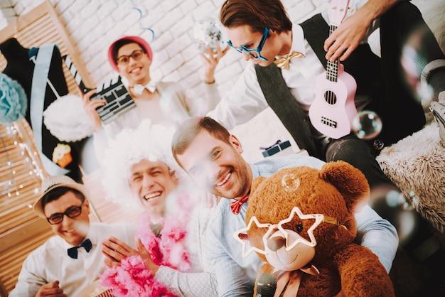 Гей-парни сидят в постели на гей-вечеринке.