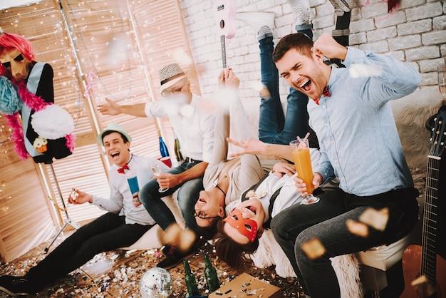 ゲイの男がパーティーでふざけてソファーでポーズします。