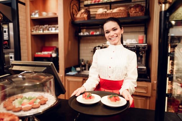 パン屋さんのケーキと一緒に立っている若い笑顔の女性。