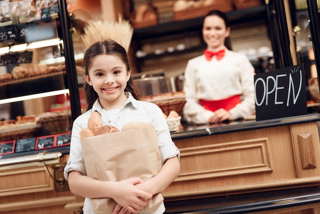 モダンなパン屋さんでパンを買う若い微笑の女の子。