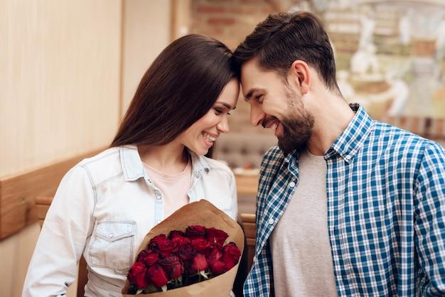 幸せな若いカップルは、現代のカフェテリアで日付を持っています。