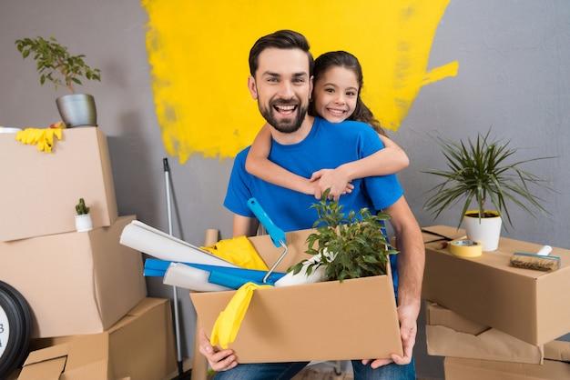 小さな娘は父親を抱きしめ、父親は道具の箱を持っています。