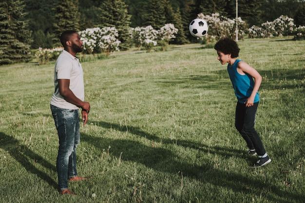 アフロの息子と父親は一緒にボールで遊ぶ。