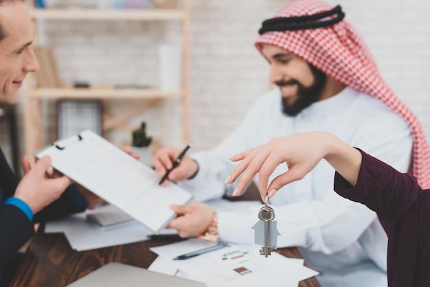 幸せな豊かなアラブ家族は家の契約に署名しました。
