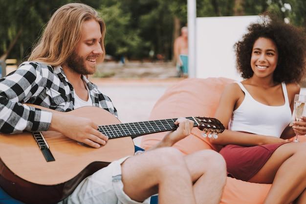 ビーチキャンプギターを弾く友達に音楽を楽しむ。