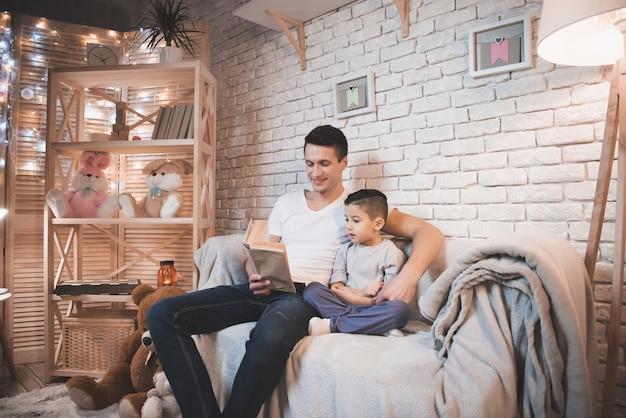Отец читает сказку своему сыну на диване.