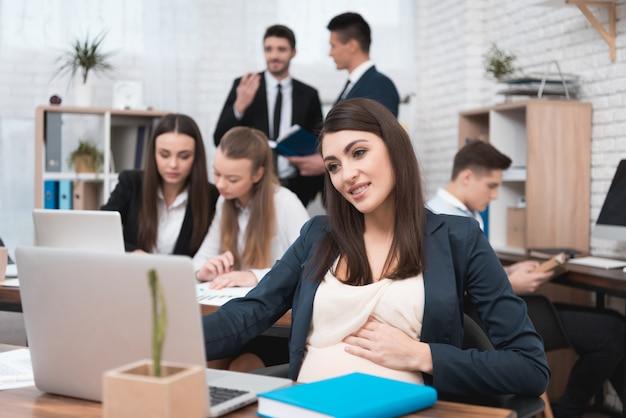 妊娠中の若い女性はオフィスの中で働いて