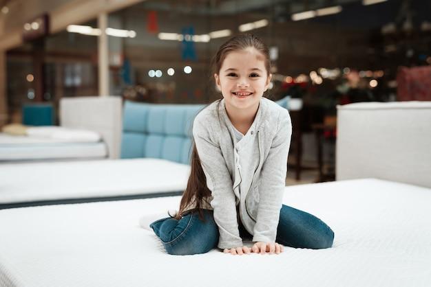 店のマットレスの上に座っている若い女の子の笑顔。