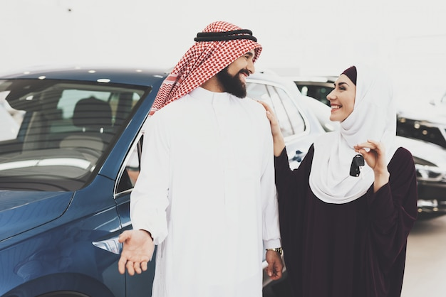 車のキーを持つ女性アラブ家族のための車を買います。