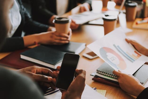 ビジネスマンやビジネスウーマンはテーブルでいくつかの仕事をしています。
