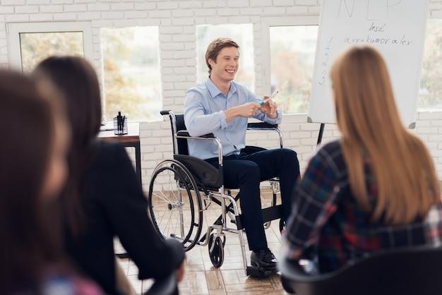 Человек в инвалидной коляске рядом с флипчартом с надписью нлп.