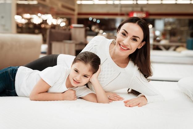 Молодая счастливая женщина и маленькая девочка на матрасе