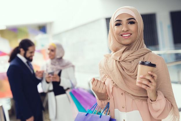ショッピングの後モールでコーヒーを飲みながら立っているアラビア人