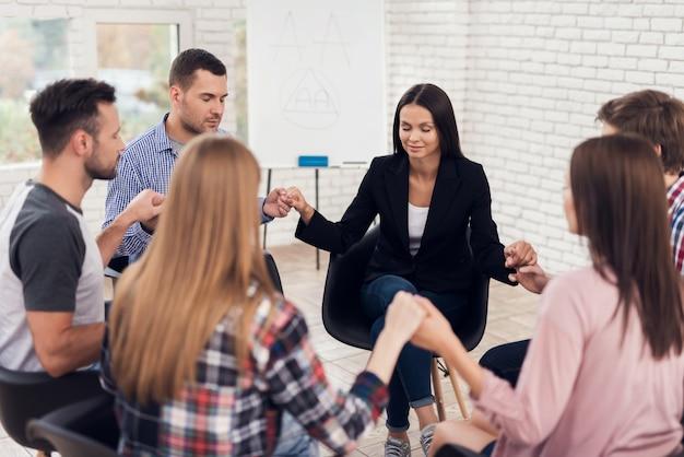 人々は座っていると治療セッションで手をつないでいます。