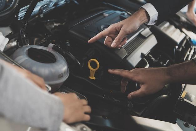 フードの下で車のエンジンを検査する人々の手。