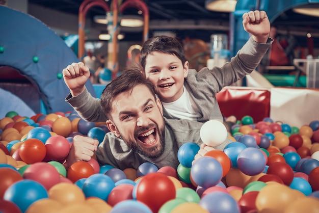 センターでボールを持つプールでお父さんと息子を楽しんでいます。