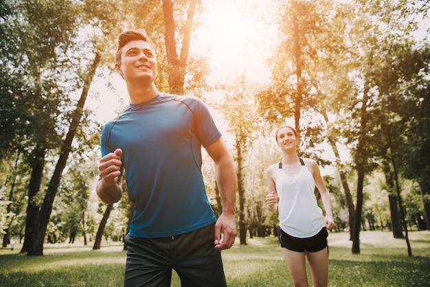 運動選手の人々はグリーンパークで走っています