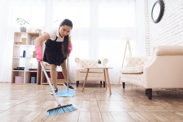 ほうきとスクープと床を掃除するタイの女の子。