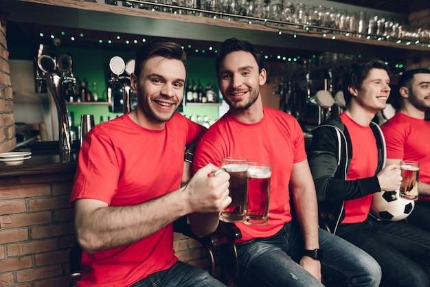 サッカーファンがビールを飲みながらゲームを見ています。
