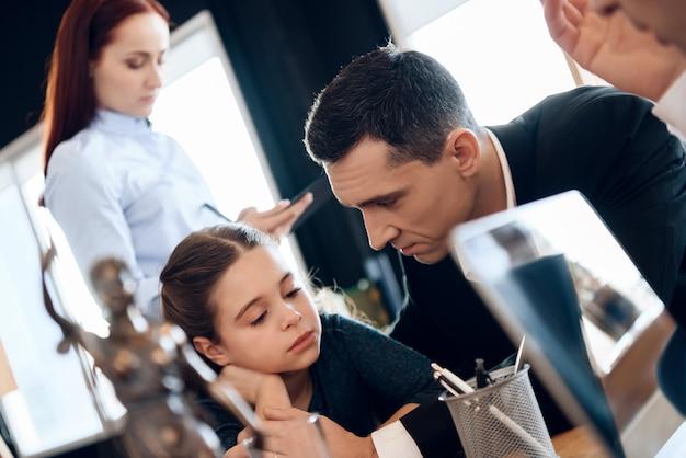 Взрослый отец успокаивает дочь, сидя за столом в офисе