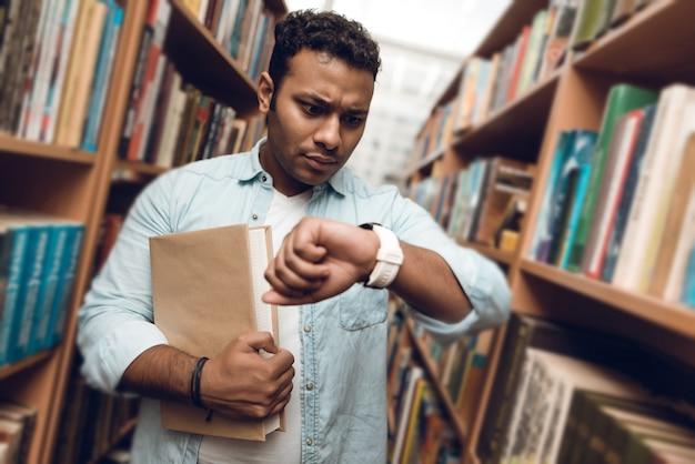 図書館の本の通路での民族のインド人混血学生。