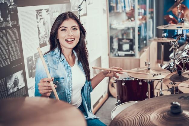 美しい少女は、ミュージックストアのドラムキットで遊んでいます。