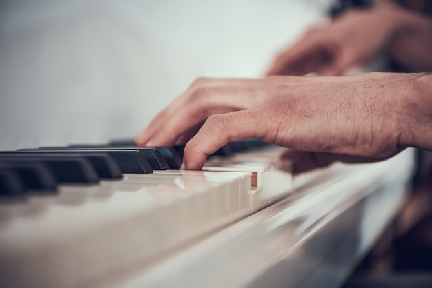 閉じる。男の手がピアノを弾きます。音楽パフォーマンス